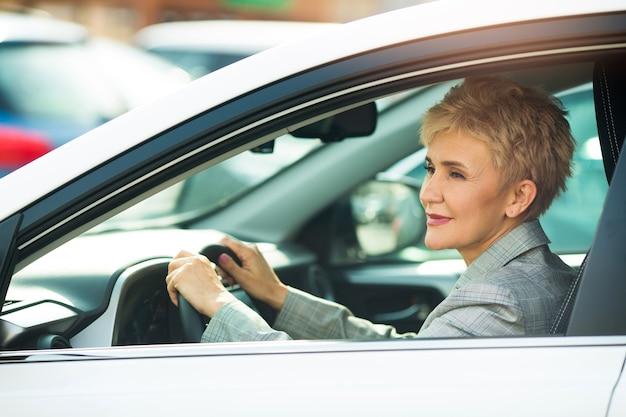 Mulher elegante em idade, de terno, sentada ao volante de um carro