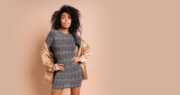 Mulher elegante em jaket de seda dourada e vestido sexy brilhante com corpo bronzeado perfeito posando sobre parede bege. saltos altos. cabelos ondulados incríveis.