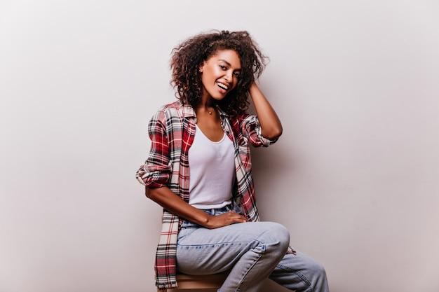 Mulher elegante em jeans vintage azul sorrindo. menina africana elegante em traje casual, desfrutando de um ensaio fotográfico.
