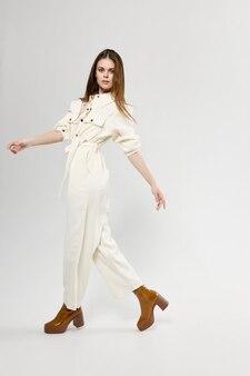 Mulher elegante em macacão branco em um modelo de emoções de roupas elegantes de fundo claro
