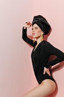 Mulher elegante em macacão preto posando na parede rosa