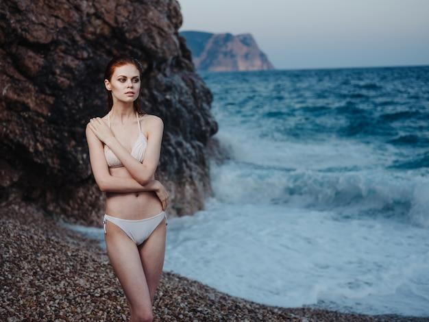 Mulher elegante em maiô branco nus ombros água transparente oceano praia natureza. foto de alta qualidade
