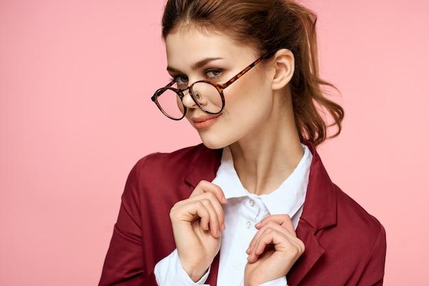 Mulher elegante em óculos de casaco vermelho gerente de escritório fundo rosa