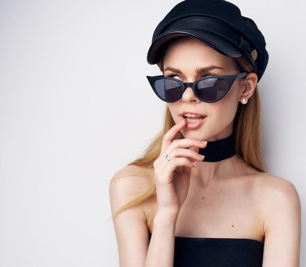 Mulher elegante em óculos de sol boné preto estúdio de moda glamour cosmetics. foto de alta qualidade