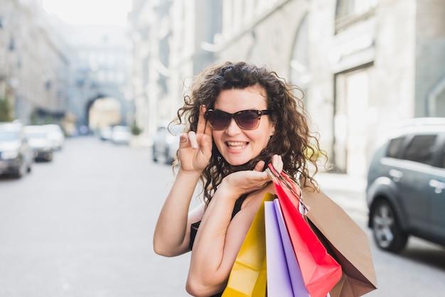 Mulher elegante em óculos de sol, carregando sacolas de compras