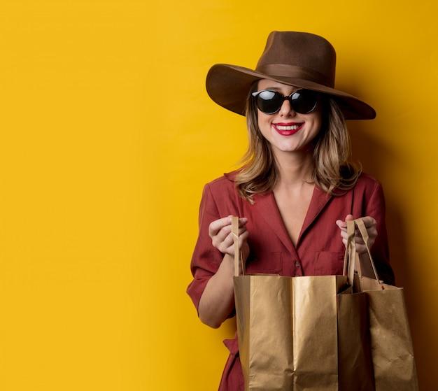 Mulher elegante em óculos de sol e com sacolas de compras