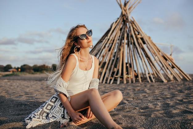 Mulher elegante em óculos de sol pretos, sentado na praia e olhando para o céu.