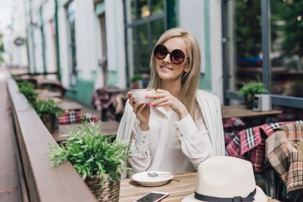 Mulher elegante em óculos de sol, sentado em um café de verão