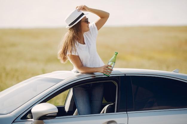 Mulher elegante em pé bin uma escotilha do carro
