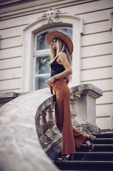 Mulher elegante em pé de chapéu branco na cidade velha
