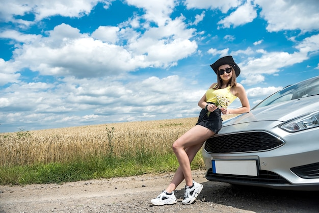 Mulher elegante em pé perto de seu carro e desfrutar da liberdade na natureza fora da cidade, horário de verão