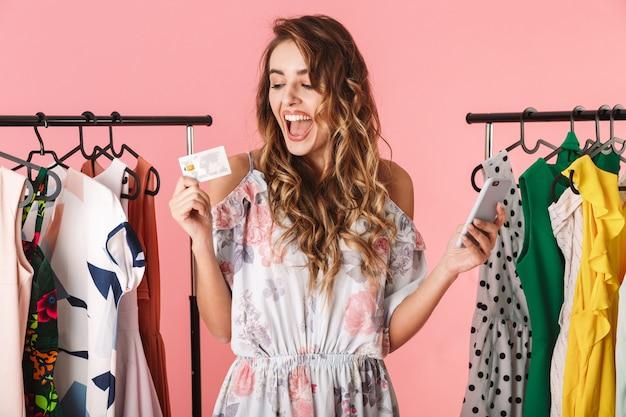 Mulher elegante em pé perto do guarda-roupa, segurando um smartphone e um cartão de crédito isolado em rosa