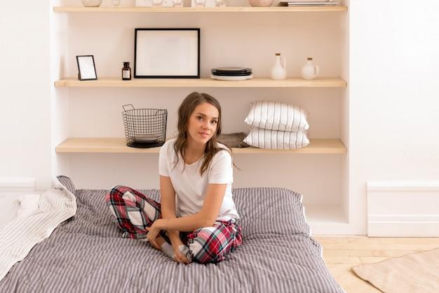 Mulher elegante em roupas para casa descansando na cama