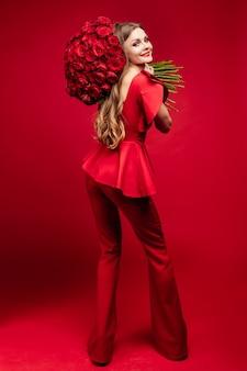 Mulher elegante em roupas vermelhas segurando flores