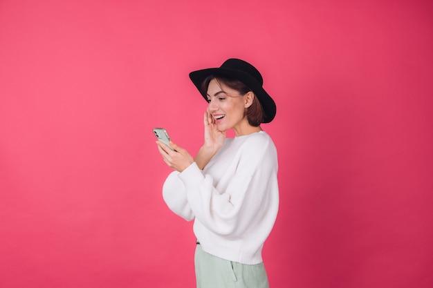 Mulher elegante em suéter branco casual e chapéu na parede rosa vermelha