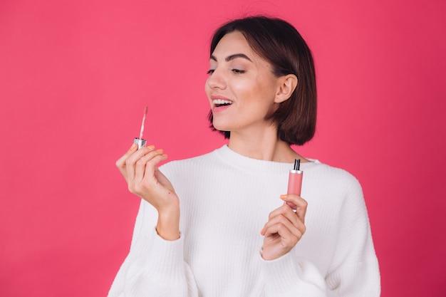 Mulher elegante em suéter branco casual na parede rosa vermelha