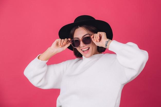 Mulher elegante em suéter branco casual, óculos escuros e chapéu na parede rosa vermelha