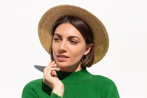 Mulher elegante em suéter verde casual e chapéu ao ar livre na parede branca sorriso calmo e confiante