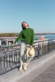 Mulher elegante em suéter verde casual e chapéu ao ar livre na ponte com vista para o rio aproveita um dia ensolarado de verão