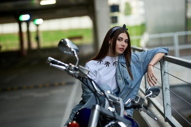 Mulher elegante em um jeans, sentado em uma motocicleta estacionada perto de um shopping center.