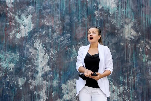 Mulher elegante em um terno de parede branca posando na parede abstrata