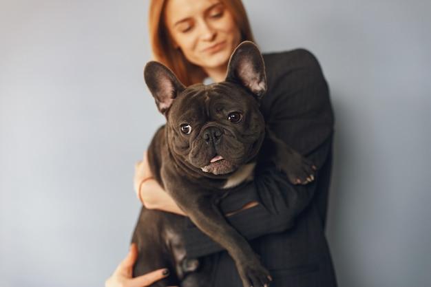 Mulher elegante em um terno preto com bulldog preto