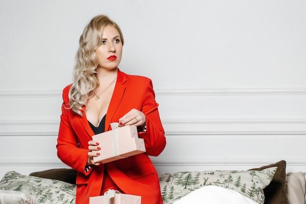 Mulher elegante em um terno vermelho segura a caixa de presente nas mãos.