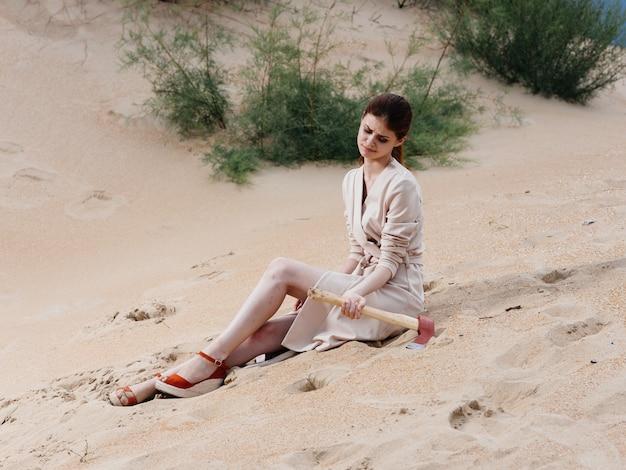 Mulher elegante em um vestido de verão com um machado nas mãos e sapatos vermelhos em pé na areia da praia