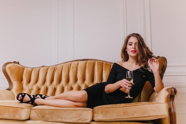 Mulher elegante em um vestido longo preto deitada no sofá marrom com expressão facial séria. retrato interior de menina arrepiante com um penteado elegante, bebendo vinho no sofá.