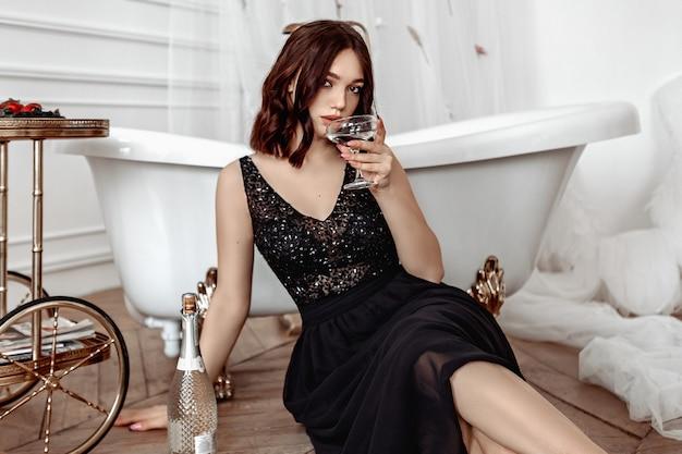 Mulher elegante em um vestido preto, bebendo vinho branco e se deitando ao lado de um luxuoso banheiro.