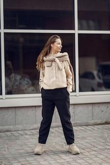 Mulher elegante em uma camisa marrom em uma cidade de primavera