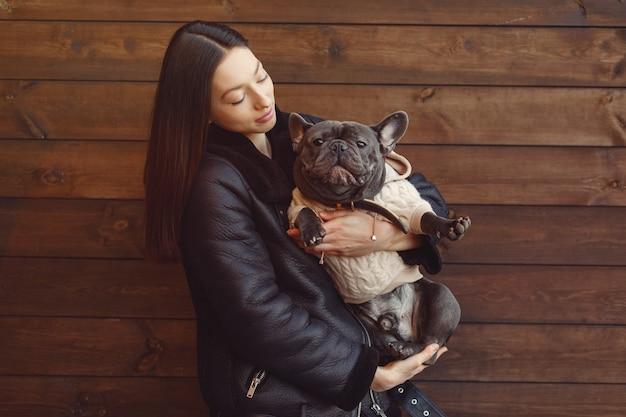 Mulher elegante em uma jaqueta preta com bulldog preto