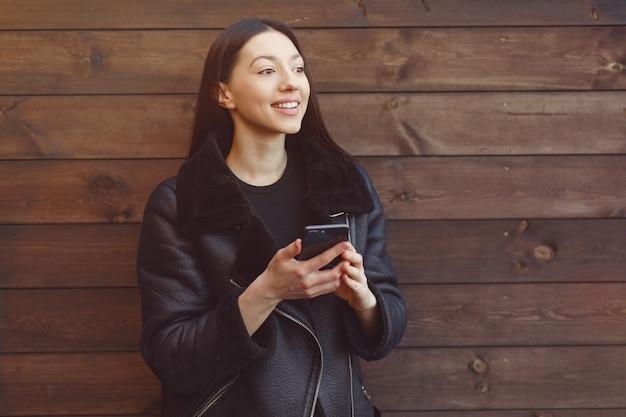 Mulher elegante em uma jaqueta preta de pé em uma parede marrom