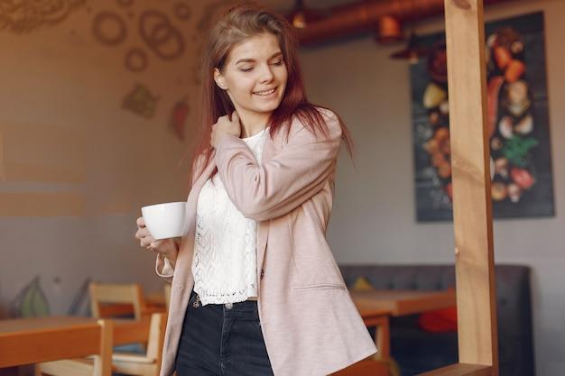 Mulher elegante em uma jaqueta rosa, passar o tempo em um café