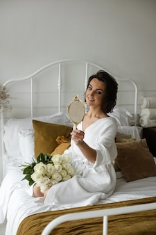Mulher elegante em vestido branco posa e se senta no sofá