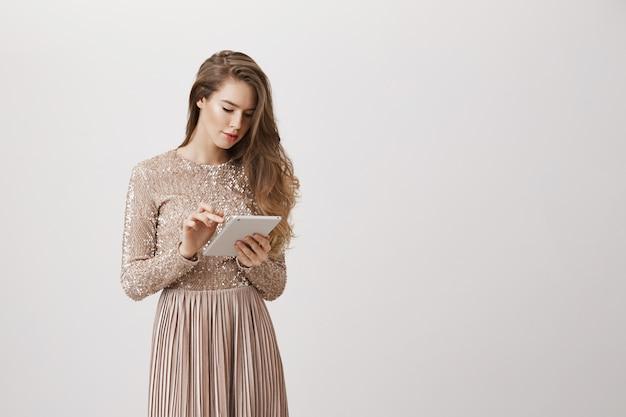 Mulher elegante em vestido de noite usando tablet digital