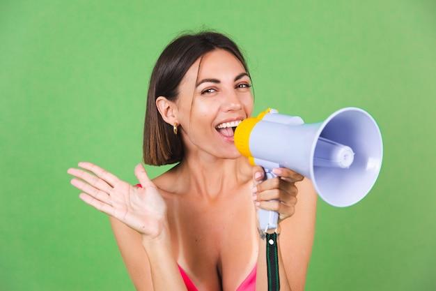 Mulher elegante em vestido de seda rosa em verde, feliz animada alegre alegre gritando no megafone, isolado