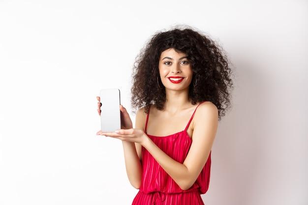 Mulher elegante em vestido vermelho e maquiagem, mostrando a tela do smartphone em branco e sorrindo, em pé sobre um fundo branco. copie o espaço