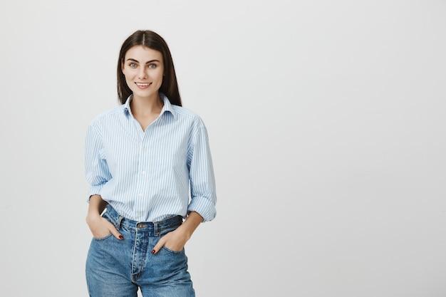Mulher elegante empresária sorrindo, com as mãos nos bolsos