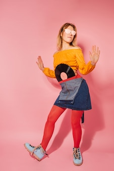 Mulher elegante estilo retro com vinil vintage em fundo rosa