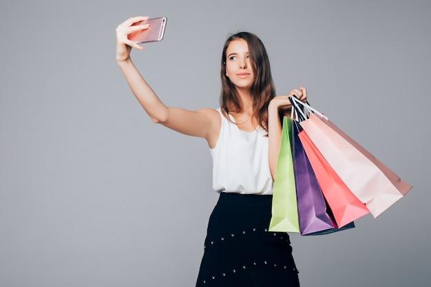 Mulher elegante fazendo selfie com sacolas de compras em fundo branco e sacolas de papel nos braços