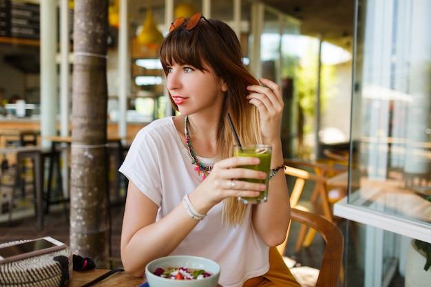 Mulher elegante feliz comendo comida saudável, sentado no belo interior com flores verdes