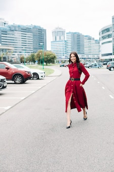 Mulher elegante feliz em vermelho na estrada