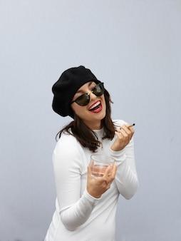 Mulher elegante fumando um baseado do lado de fora com distância cinza