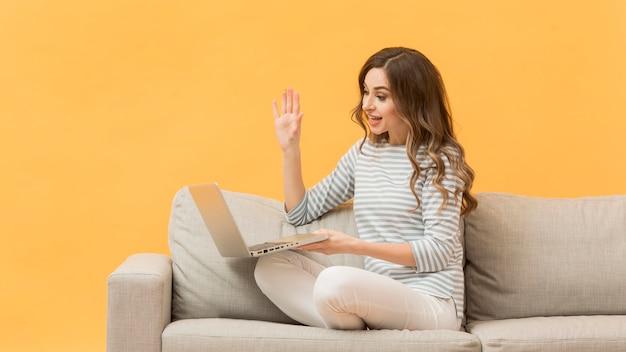 Mulher elegante, gravando-se no sofá