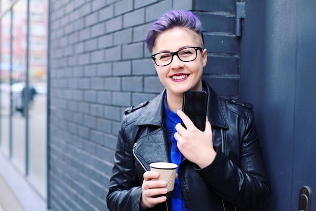 Mulher elegante hipster usando mensagens de texto de telefone no aplicativo de smartphone em uma rua com uma xícara de café