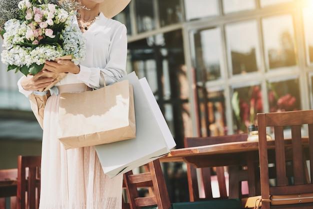 Mulher elegante irreconhecível em pé perto de café de rua com buquê de flores