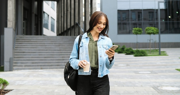 Mulher elegante jovem alegre caucasiana andando pela rua, tocando ou rolando no smartphone e tomando uma bebida quente pela manhã. linda feliz mensagem de texto feminina no telefone e bebendo café.