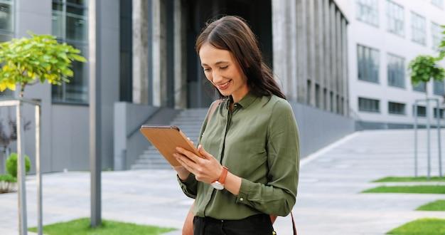 Mulher elegante jovem alegre caucasiana tocando ou rolando no dispositivo tablet na rua. linda mulher feliz usando computador gadget. lado de fora. assistindo às redes sociais.