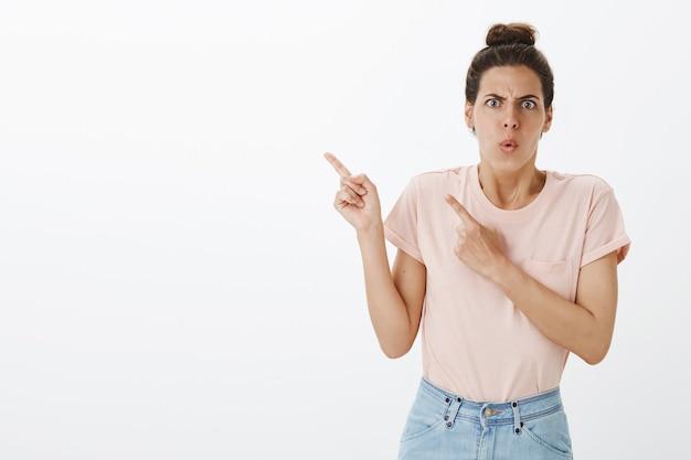 Mulher elegante jovem confusa e com raiva posando contra a parede branca